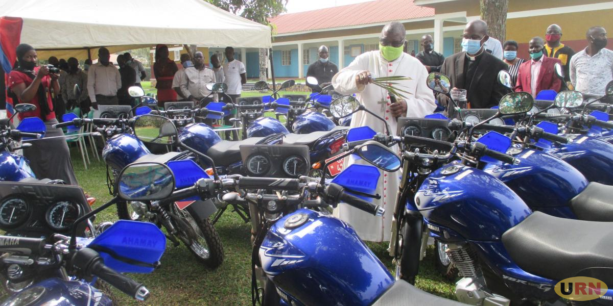 Bishop Paul Ssemogerere blesses the 18 motorcycles to be used in Global Climate project, following him is Fr. Hilary Muheezangango